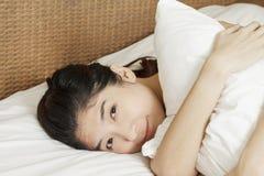 睡觉在床上的年轻美丽的妇女,在早晨 免版税库存图片