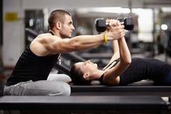 个人健身房的教练员帮助的妇女 图库摄影