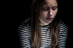 一个沮丧的青少年的女孩的黑暗的画象 图库摄影