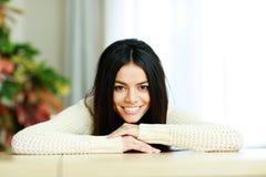 倾斜在桌的快乐的年轻微笑的妇女 免版税库存图片