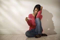 看妊娠试验的哀伤的亚裔女孩坐地板 免版税库存照片