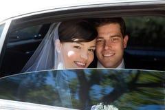 在大型高级轿车的婚礼夫妇 图库摄影