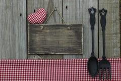 与红色方格花布心脏的空白的木标志和桌布和生铁匙子和叉子 免版税库存图片