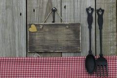 与红色方格花布桌布的空白的木标志、金心脏和生铁匙子和叉子有木背景 免版税图库摄影