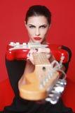 Γυναίκα στο κόκκινο υπόβαθρο με την ηλεκτρική κιθάρα Στοκ εικόνα με δικαίωμα ελεύθερης χρήσης