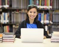 亚裔妇女在有膝上型计算机的图书馆里 免版税图库摄影