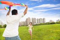 演奏五颜六色的风筝的愉快的家庭在城市公园 库存图片