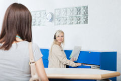 接待员看妇女在牙医的办公室 免版税库存图片