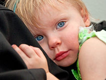 疲乏的两岁的女孩偎依的父母 免版税库存照片