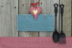与心脏的古色古香的空白的蓝色标志、方格花布桌布和生铁匙子和叉子 库存图片