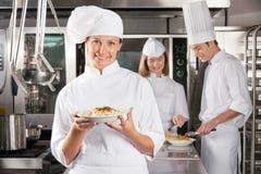 当前盘的愉快的厨师在工业厨房里 免版税库存图片
