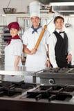 确信的厨师和侍者在厨房里 免版税图库摄影