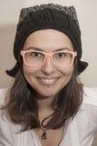 与冬天帽子和夏天玻璃的滑稽的微笑的女孩画象 免版税库存图片