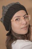 时髦的女孩画象被编织的帽子的有滑稽的玻璃的 库存照片