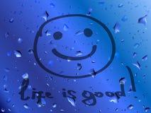 微笑。生活是好。在湿玻璃的题字 免版税库存图片