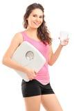 拿着杯水和重量标度的美丽的妇女 免版税库存照片