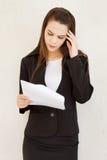 拿着她的头的紧张女性商业主管手 免版税库存图片