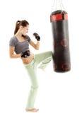 Атлетическая женщина пиная грушу Стоковое фото RF