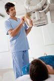 Техник принимая рентгеновский снимок пациента Стоковое Изображение