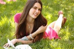 在绿色的有吸引力的愉快的微笑的学生青少年的女孩阅读书 免版税库存图片