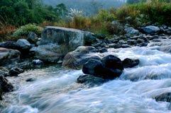 流经岩石的河水在黎明 免版税图库摄影