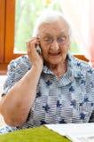 资深在手机的妇女拨的数字 免版税库存照片