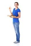 Νέα περιστασιακή γυναίκα σπουδαστών με το βιβλίο και την υπόδειξη επάνω. Στοκ Εικόνες