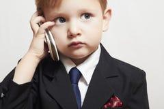 Μικρό παιδί στο επιχειρησιακό κοστούμι με το τηλέφωνο κυττάρων. όμορφο παιδί. μοντέρνο παιδί Στοκ Εικόνα