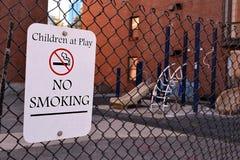 Παιδιά στο παιχνίδι - απαγόρευση του καπνίσματος ως μήνυμα προειδοποίησης, σημάδι στο μέταλλο, Στοκ Φωτογραφία