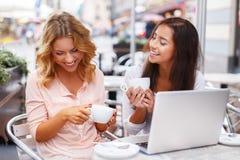有膝上型计算机的两个女孩 免版税库存照片