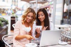 有膝上型计算机的两个女孩 免版税库存图片