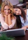 有膝上型计算机的两个女孩 库存图片