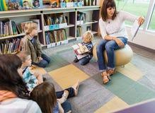 老师对孩子的阅读书在图书馆里 免版税库存照片