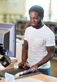 工作在柜台的图书管理员在书店 免版税库存照片
