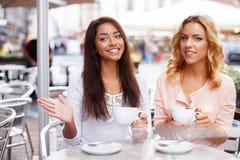 咖啡馆的两个美丽的女孩 图库摄影