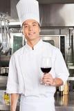 拿着杯红葡萄酒的厨师 免版税库存图片