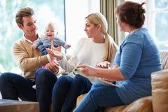 与年轻婴孩的社会工作者参观的家庭 免版税图库摄影