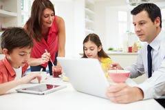 使用数字式设备的家庭在早餐桌上 免版税图库摄影