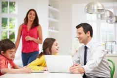 使用数字式设备的家庭在早餐桌上 库存照片