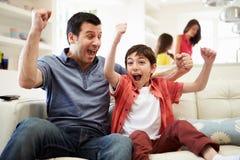 在电视的父亲和儿子观看的体育 免版税库存图片