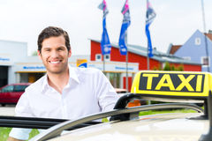 在出租汽车等待的客户前面的司机 免版税库存图片
