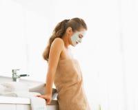 Молодая женщина с косметической маской на стороне в ванной комнате Стоковые Изображения