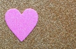 在金子闪烁背景的桃红色心脏。情人节卡片 库存照片