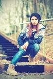 帽子的孤独的女孩少年坐台阶和哀伤的秋天 免版税图库摄影