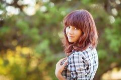 年轻可爱的金发微笑的妇女画象夏天绿色公园的。 库存照片