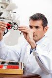 Глазной врач проверяя объектив пробных рамок Стоковые Изображения RF