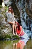倾斜在河旁边的岩石的两个美丽的少妇 库存图片