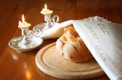安息日图象。鸡蛋面包面包和坎德拉在木桌上 免版税库存照片