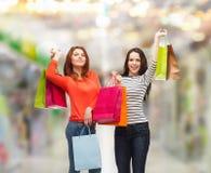 有购物袋的两个微笑的十几岁的女孩 图库摄影