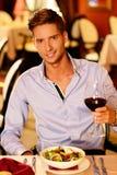 有杯的英俊的年轻人红葡萄酒 免版税库存图片